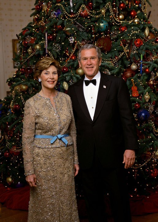 "President George W. Bush and Laura Bush stand in front of the official White House Christmas Tree during the 2004 holiday season in the Blue Room of the White House. The White House celebrates the holidays with, ""A Season Of Merriment and Melody,"" and include items like 350 instrument ornaments that adorn the Blue Room tree. White House photo by Eric Draper"