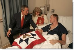 President George W. Bush visits with USMC Lance Corporal Sean Phillips and his mother, Sharon, at the National Naval Medical Center in Bethesda, Md., Saturday, Dec. 11, 2004. Cpl. Phillips was injured in Operation Iraqi Freedom. While recovering in Germany, he received a donated quilt from supporters in Texas. Given to wounded soldiers returning to the states, the quilts come from groups and individuals from all over America. The President added his own Texas signature to the quilt. White House photo by Paul Morse