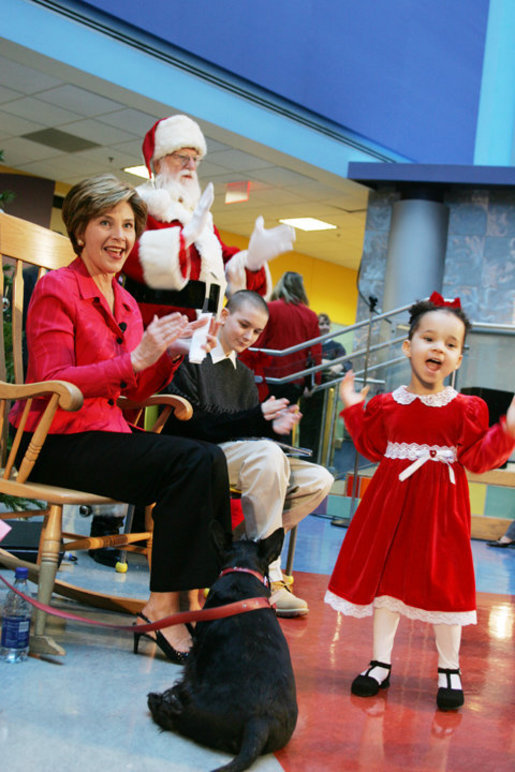 Mrs. Bush and Taylor Buckles, older sister of conjoined twins successfully separated earlier this year, react to the first viewing of the 2004 BarneyCam during a children's holiday program at the Children's National Medical Center in Washington, D.C., Wednesday, Dec., 15, 2004. White House photo by Susan Sterner