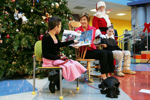 "Mrs. Bush reads ""Dream Snow"" by Eric Carle with help from her patient escorts, Brandy Robinson, left, and Keith ""Koddie"" Hernandez during the annual Children's National Medical Center holiday program in Washington, D.C., Wednesday, Dec. 15, 2004. White House photo by Susan Sterner"