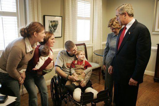 President George W. Bush and Laura Bush talk with U.S. Army Sgt. Dale Beatty of Statesville, N.C., and, from left, sister-in-law Wendolyn Summers, wife Belinda Beatty, son Lucas, 6 months old, and son Dustin, 2 years old, during a visit to the Fisher House at Walter Reed Army Medical Center in Washington, D.C., Tuesday, Dec. 21, 2004. President Bush presented Sgt. Beatty The Purple Heart for injuries he sustained while serving in Operation Iraqi Freedom. White House photo by Paul Morse