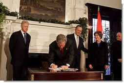 President George W. Bush signs a condolence book for the victims of the recent tsunami during a visit to the Embassy of India in Washington, D.C., Monday, Jan. 3, 2005. Also signing to express their condolences are Laura Bush and former Presidents Bush and Clinton.  White House photo by Susan Sterner