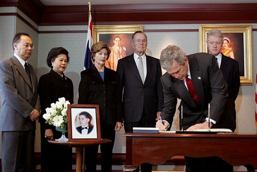 President George W. Bush signs a condolence book for the victims of the recent tsunami during a visit to the Embassy of Thailand in Washington, D.C., Monday, Jan. 3, 2005. Next to the book, stands a photograph of Khun Poom Jensen, 21. A grandson of Thailand's King Bhumibol Adulyadej, Mr. Jensen died in the tsunami. Also signing their condolences are Laura Bush and former Presidents Bush and Clinton. White House photo by Susan Sterner.