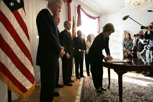 Laura Bush signs a condolence book for the victims of the recent tsunami during a visit to the Embassy of Sri Lanka in Washington, D.C., Monday, Jan. 3, 2005. Also signing to express their condolences are President George W. Bush and former Presidents Clinton and Bush. White House photo by Eric Draper.