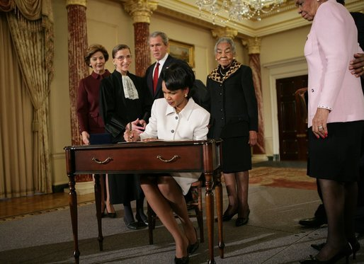 Secretary of State Dr. Condoleezza Rice signs official papers Friday, Jan. 28, 2005, after receiving the oath of office during her ceremonial swearing in at the Department of State. Watching on are, from left, Laura Bush, Justice Ruth Bader Ginsburg, President George W. Bush and an unidentified family member. White House photo by Eric Draper