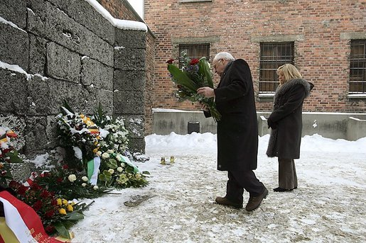 Vice President Dick Cheney, flanked by his daughter Liz Cheney, places a bouquet of flowers at the Wall of Death at the Auschwitz-1 Nazi concentration camp, near Krakow, Poland, Friday, Jan. 28, 2005. Vice President Cheney was there to take part in ceremonies commemorating the 60th Anniversary of the liberation of the Auschwitz camps. The Wall of Death was named for its use as the backdrop for firing squads where thousands of prisoners were executed while the camp was in operation. White House photo by David Bohrer