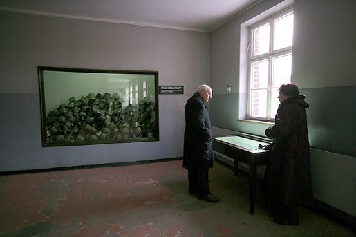 Standing in a room formerly used as barracks for Nazi prisoners, a museum guide explains to Vice President Dick Cheney about the atrocities committed there at the Auschwitz-1 Nazi concentration camp, near Krakow, Poland, Friday, Jan. 28, 2005. The window at left shows a display of empty cans of Zyklon-B gas used against former prisoners. Vice President Cheney was there to take part in ceremonies commemorating the 60th Anniversary of the liberation of the Auschwitz camps. White House photo by David Bohrer