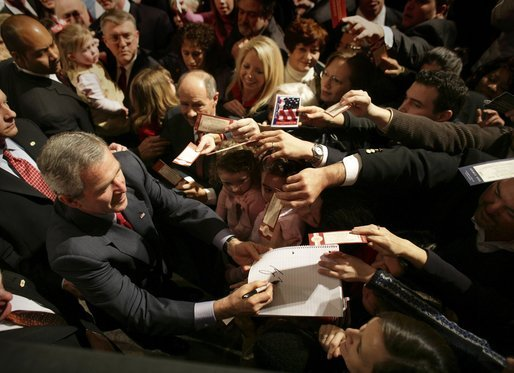 President George W. Bush autographs mementos after participating in a discussion on strengthening Social Security in Little Rock, Ark., Friday, Feb. 4, 2005. White House photo by Eric Draper