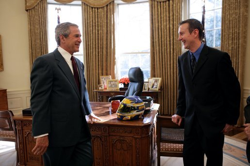 President George W. Bush talks with Kurt Busch, the 2004 Nextel Cup Nascar champion, during a visit by him and other racing officials to the Oval Office Feb. 7, 2005. President Bush was presented a racing helmet by Mr. Busch during the visit. White House photo by Eric Draper