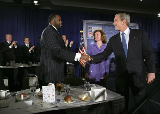 President George W. Bush greets Detroit Mayor Kwame Kilpatrick after delivering remarks at the Detroit Economic Club in Detroit, Michigan, Tuesday, Feb. 8, 2005. Also pictured at center is Detroit Economic Club President Beth Chappell. White House photo by Eric Draper.