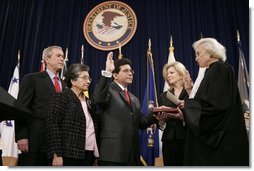 Justice Sandra Day O'Connor offers Alberto Gonzales the oath of office Monday, Feb. 14, 2005, during his ceremonial swearing-in at the Justice Department. With President George W. Bush looking on are Mr. Gonzales's mother, Maria, and wife, Becky.  White House photo by Paul Morse