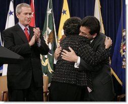 As President Bush leads the applause, Attorney General Alberto Gonzales embraces his mother, Maria, after he was ceremoniously sworn into office Monday, Feb. 14, 2005, at the Justice Department.  White House photo by Paul Morse