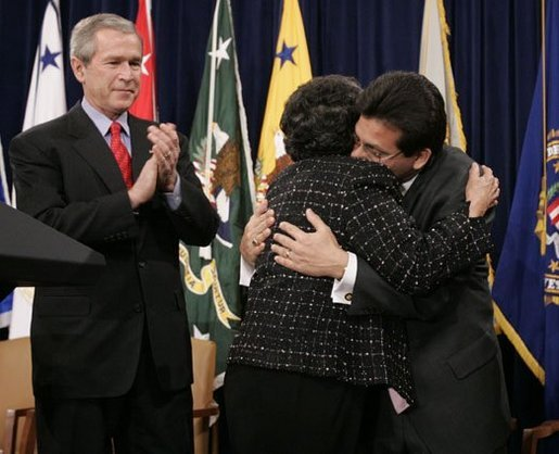 As President Bush leads the applause, Attorney General Alberto Gonzales embraces his mother, Maria, after he was ceremoniously sworn into office Monday, Feb. 14, 2005, at the Justice Department. White House photo by Paul Morse.