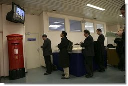 Staff members watch via television from a holding room as President George W. Bush and NATO Secretary General Jaap de Hoop Scheffer speak during a Feb. 22, 2005 joint news conference at NATO headquarters in Brussels.  White House photo by Eric Draper