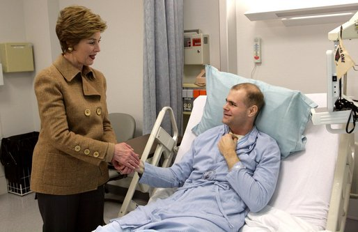 Laura Bush visits with U.S. Army Specialist Garrett Larson who is recovering from injuries sustained in Iraq at the Landstuhl Regional Medical Center Tuesday, Feb. 22, 2005, in Ramstein, Germany. White House photo by Susan Sterner