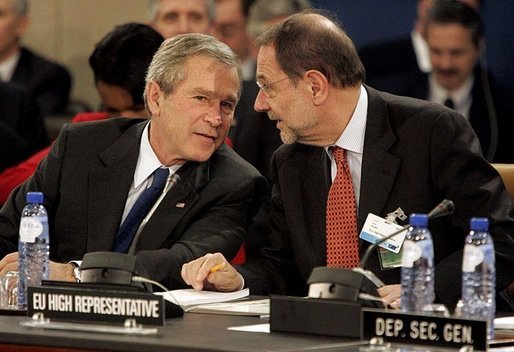 President George W. Bush speaks with European Union High Representative Javier Solana during a plenary session of the North Atlantic Council at NATO Headquarters in Brussels Tuesday, Feb. 22, 2005. White House photo by Eric Draper