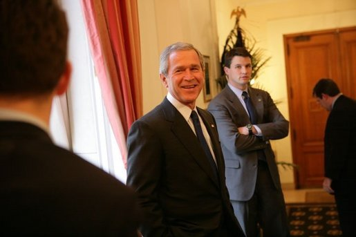 President George W. Bush speaks with staff before a meeting Tuesday, Feb. 22, 2005, at the Ambassador's Residence in Brussels. White House photo by Eric Draper