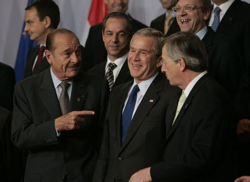 President George W. Bush talks with French President Jacques Chirac, left, and European Union President Jean-Claude Juncker as world leaders take their places for the official NATO group photo in Brussels Tuesday, Feb. 22, 2005. White House photo by Eric Draper