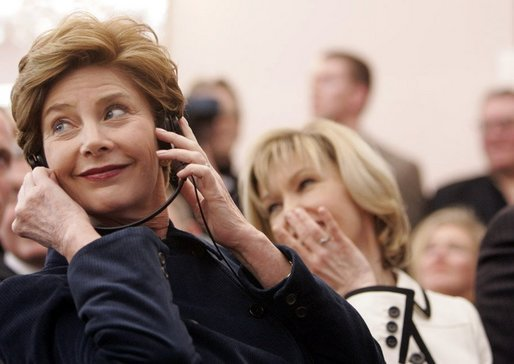 Laura Bush listens to translation headphones during a joint press conference with President George W. Bush and German Chancellor Gerhard Schroeder at the Electoral Palace in Mainz, Germany, Wednesday, Feb. 23, 2005. The Chancellor's wife, Mrs. Schroeder-Koepf is seated next to Mrs. Bush. White House photo by Eric Draper