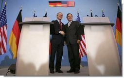 President George W. Bush shakes hands with German Chancellor Gerhard Schroeder during a Feb. 23, 2005, joint press conference at the Electoral Palace in Mainz, Germany.   White House photo by Eric Draper