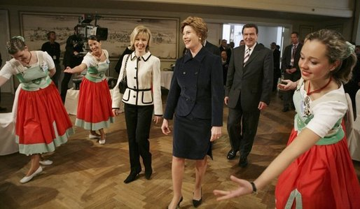 Laura Bush watches dancers during a Wednesday, Feb. 23, 2005, lunch hosted by Chancellor Gerhard Schroeder, behind, and Mrs. Schroeder-Koepf, left, at the Electoral Palace in Mainz, Germany. White House photo by Eric Draper