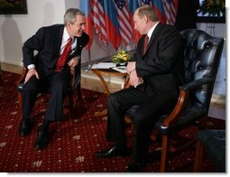 President George W. Bush leans in to speak with Russia President Vladimir Putin Thursday, Feb. 24, 2005 during a photo opportunity in Bratislava, Slovakia. The meeting of the two leaders marked the last during President Bush's five-day European trip.   White House photo by Eric Draper