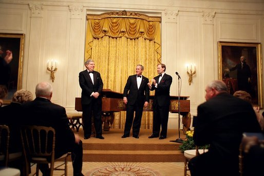 President George W. Bush thanks composer Marvin Hamlisch, left, and entertainer Mark McVey for their performance during the state dinner for the National Governors Association at the White House Sunday, Feb. 27, 2005. White House photo by Paul Morse