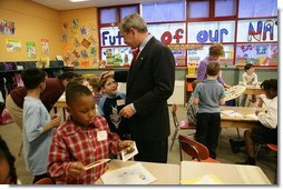 President George W. Bush talks with Kasey Stevenson and other students as he signs autographs during a visit to an after-school classroom program at the Providence Family Support Center in Pittsburgh Monday, March 7, 2005.   White House photo by Susan Sterner