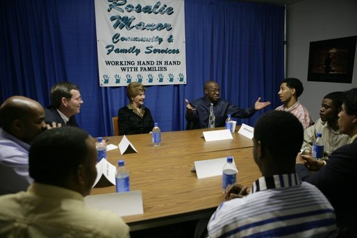 Laura Bush Secretary of Health and Human Services Mike Leavitt listen to Alphonso Pettis, Case Manager for Today's Dad's at Rosalie Manor Community and Family Services center in Milwaukee, Wis, Tuesday, March 8, 2005. Mr. Pettis is explaining in detail the pride he feels regarding the achievements of the young men sitting at the table, who, as teen fathers, have finished high school and found jobs. White House photo by Susan Sterner