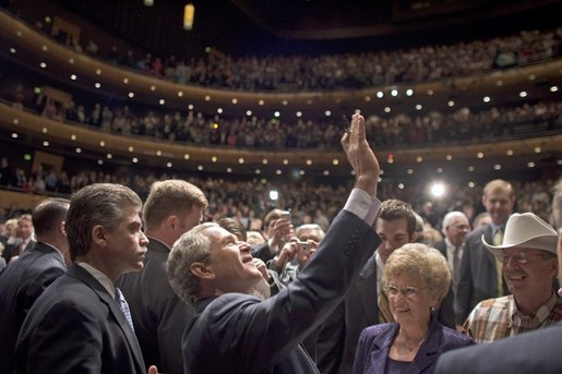 President George W. Bush waves to people in the balconies after participating in a conversation on strengthening Social Security at the Cannon Center for the Performing Arts in Memphis, Tenn., Friday, March 11, 2005. White House photo by Paul Morse