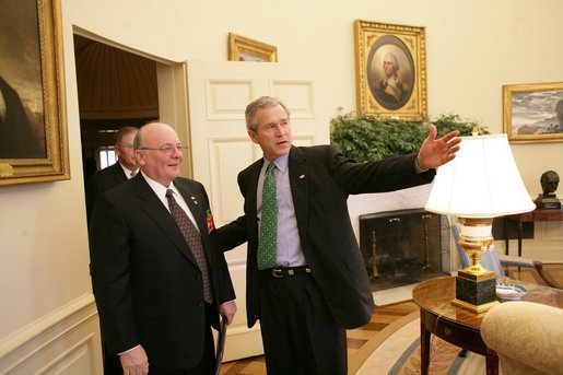 President George W. Bush talks with U.S. Army veteran Tom Cadmus, the National Commander of the American Legion, in the Oval Office Thursday, March 17, 2005. White House photo by Eric Draper