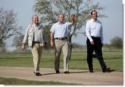 Hosting a lunch and tour at his ranch, President George W. Bush waves to the press while walking with Canadian Prime Minister Paul Martin, left, and Mexican President Vicente Fox in Crawford, Texas, March 23, 2005.  White House photo by Eric Draper