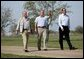 Hosting a lunch and tour at his ranch, President George W. Bush waves to the press while walking with Canadian Prime Minister Paul Martin, left, and Mexican President Vicente Fox in Crawford, Texas, March 23, 2005. White House photo by Eric Draper White House photo by Eric Draper