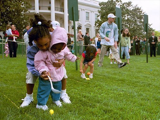 A helping hand is given during the Easter egg roll where little competitors use a spoon to carry a hard-boiled egg through the South Lawn race course and across the finish line at the White House Easter Egg Roll Monday, April 21, 2003. File photo. White House photo by Susan Sterner