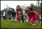 Slipping and sliding, eggs are tossed in rainy race on the South Lawn during the 2004 White House Easter Egg Roll Monday, April 12, 2004. Because of inclement weather, the annual event closed at noon. File photo. White House photo by Paul Morse