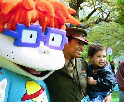 "A United States Marine and her son stand for pictures with Chuckie, a character from the cartoon, ""Rugrats,"" during the White House Easter Egg Roll Monday, April 21, 2003. More than 30 children's characters wandered through the South Lawn during the day's festivities, including Clifford the Big Red Dog, Winnie the Pooh and the Berenstain Bears. File photo. White House photo by Jennifer Smith"
