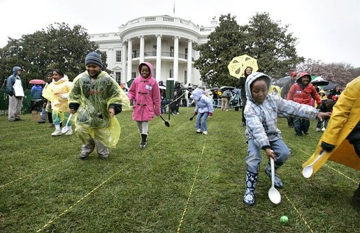 Children slip through a race with their Easter eggs during the traditional race on the South Lawn. Although rainy weather cut short the event, children and their parents made many colorful memories to brighten up a gray, gloomy day. White House photo by Paul Morse