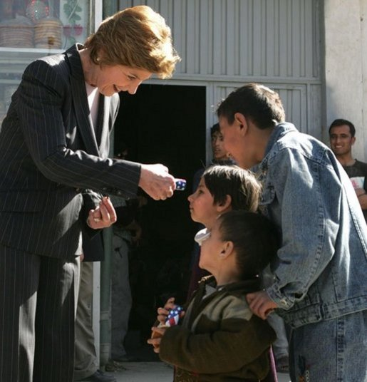 Laura Bush hands red, white and blue kaleidoscopes to youngsters outside a Kabul bakery Wednesday, March 30, 2005 during her visit to Afghanistan. White House photo by Susan Sterner