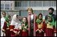 Mrs. Laura Bush stands with a group of Afghan girls on hand to greet her Wednesday, March 30, 2005, upon her arrival in Kabul. White House photo by Susan Sterner