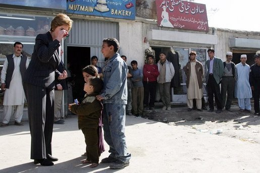 Laura Bush shows youngsters how to use a kaleidoscope outside a Kabul bakery after a stop Wednesday, March 30, 2005. The toys were gifts from the White House given by the first lady during her brief visit to Afghanistan. White House photo by Susan Sterner