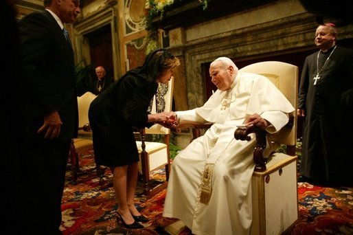 Mrs. Bush takes the hand of Pope John Paul II during the June 2004 visit to Rome by she and President Bush during which they presented the Pope with the Medal of Freedom White House photo by Eric Draper