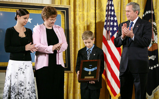 David Smith, 11-year-old son of Sgt. 1st Class Paul Smith, holds his father's Medal of Honor, awarded Monday, April 4, 2005, posthumously by President Bush during ceremonies at the White House. Looking on are Smith's wife, Birgit, and step-daughter Jessica.White House photo by Paul Morse