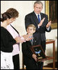 Young David Smith holds his father's Medal of Honor -- presented by President Bush -- as he looks to his mother, Birgit Smith, during ceremonies Monday, April 4, 2005, at the White House. Sgt. 1st Class Paul Smith, was mortally wounded while saving other members of his task force during Operation Iraqi Freedom.White House photo by Paul Morse