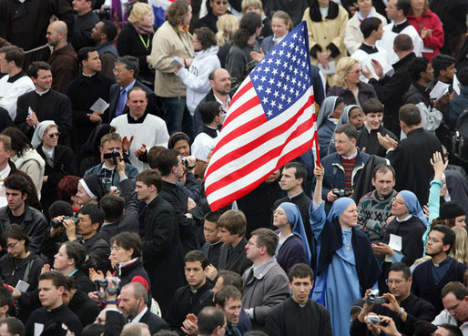 An American flag flies high above the throng of mourners inside St. Peter's square Friday, April 8, 2005, as thousands attend funeral mass for Pope John Paul II, who died April 2 at the age of 84.White House photo by Eric Draper