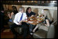 President George W. Bush takes a seat with a couple patrons at the Rockaway Athletic Club after addressing state legislators in Columbia, S.C., April 18, 2005. White House photo by Paul Morse