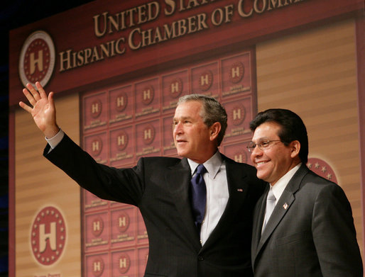 President George W. Bush stands with Attorney General Alberto Gonzales as they acknowledge the applause after the President addressed the Hispanic Chamber of Commerce Legislative Conference Wednesday, April 20, 2005, in Washington, D.C. White House photo by Eric Draper