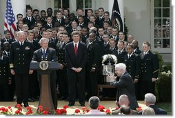 President George W. Bush and the Midshipmen of the U.S. Naval Academy's football team, break out in laughter as Sen. John McCain, R-Ariz., acknowledges his late arrival Wednesday, April 20, 2005, to the Rose Garden presentation of the Commander-in-Chief Trophy. The trophy is awarded after each season to the service academy with the best overall record against the other two. White House photo by Paul Morse