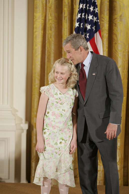 President George W. Bush congratulates Allyson Lien, 11, of Humann Elementary School in Lincoln, Neb., on receiving the President's Environmental Youth Award in the East Room of the White House April 21, 2005. White House photo by Paul Morse