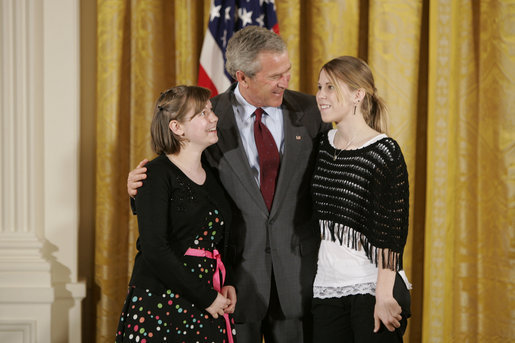 President George W. Bush congratulates eighth grade students of 2004 from Grant Community Middle School in Salem, Ore., on receiving the President's Environmental Youth Award in the East Room of the White House April 21, 2005. Members include, from left to right, Alyssa Foster, 15, and Amber Urban, 15. White House photo by Paul Morse