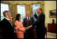 White House Chief of Staff Andrew Card swears in John Negroponte as the first Director of National Intelligence as President George W. Bush looks on Thursday, April 21, 2005, in the Oval Office. Dina Powell, Assistant to the President for Presidential Personnel, holds the Bible. White House photo by Eric Draper